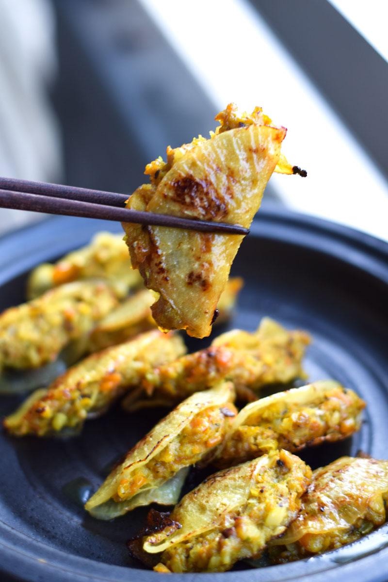 eating one healthy gyoza with chopsticks