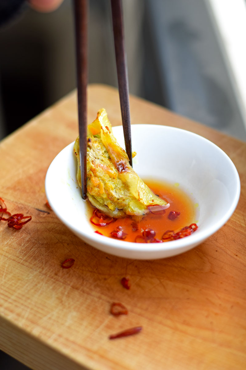 healthy potsticker dipped in sauce with chopsticks