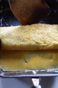 roll tamagoyaki in pan with spatula