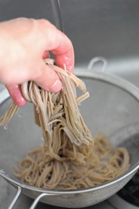 rinsing soba noodles in cold water