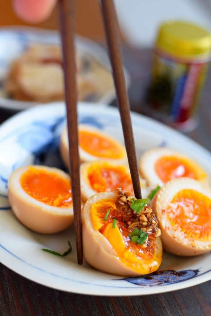 chopsticks pinching ramen egg with soy sauce rayu topping