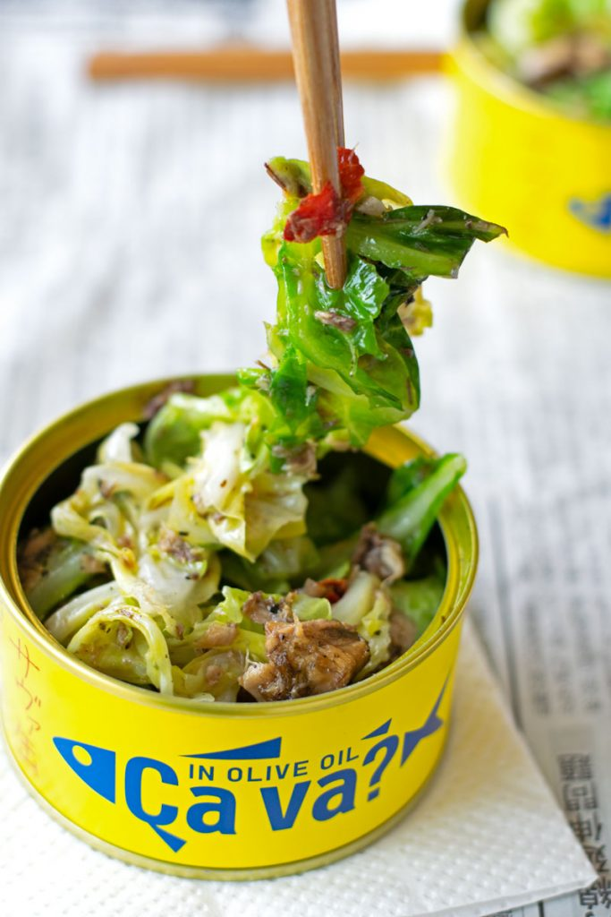 eating Italian-style izakaya side dish from a fish can with chopsticks